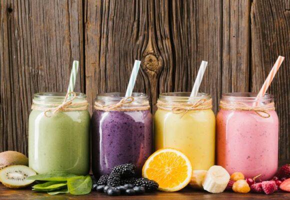 alimentos-composicao-colorida-de-frutas-e-smoothies-em-fundo-de-madeira